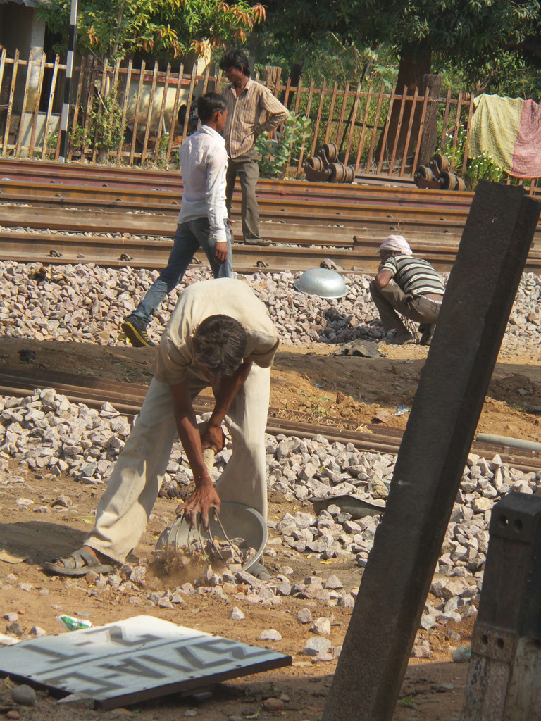 A man gathers rocks for track repairs.